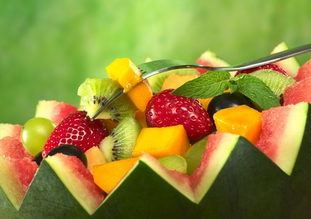 Fresh fruit salad (strawberry, kiwi, mango, grape) in melon bowl with kiwi and mango on fork and a mint leaf as garnish in front of green background (Selective Focus, Focus on the fruit on the fork and the mint leaf)