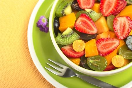 ensalada de frutas: Ensalada de frutas frescas y sanas con fresa, kiwi, uva, mango y physalis en un recipiente con horquilla y peque�as flores de color azul fotografiados desde arriba (enfoque selectivo, enfoque desde el frente a la media del taz�n)