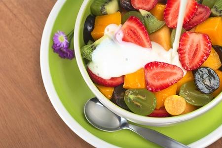 ensalada de frutas: Ensalada de frutas frescas y sanas con fresa, kiwi, uva, mango y physalis en un recipiente con yogurt simple se vierte sobre