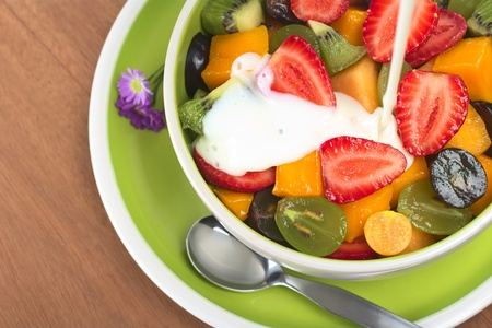 fruit salads: Fresh and healthy fruit salad with strawberry, kiwi, grape, mango and physalis in a bowl with plain yoghurt being poured over