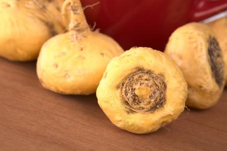 maca: Ginseng peruano (Maca SP., lat. Lepidium meyenii) que se utiliza ampliamente en Per� para sus diversos efectos sobre la salud y alto valor nutritivo con una taza de t� rojo en la parte posterior en madera (enfoque selectivo, centrarse en la ra�z del frente)