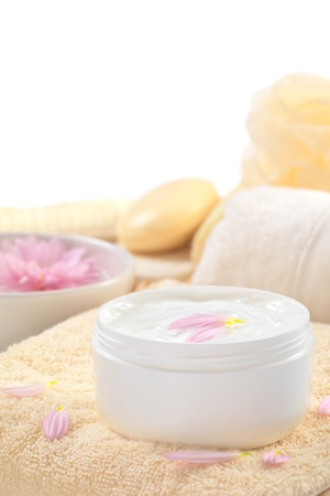 face cream: Soft body, hand and face cream with pink petals on top in a bathroomspa setting (Selective Focus, Focus on the horizontalback petal on the cream) Stock Photo