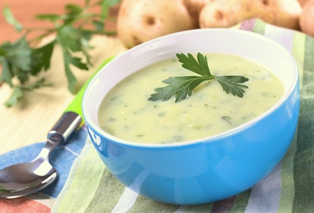 potato soup: Cream of potato with herbs and green onions garnished with parsley and served in a blue bowl with potatoes and parsley in the back (Selective Focus, Focus on the front of the parsley)