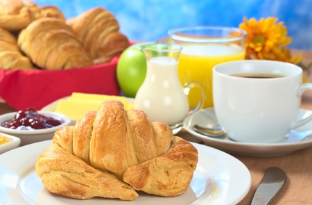 continental breakfast: Continental breakfast with croissant, coffee, orange juice, milk, jam, butter and green apple (Selective Focus, Focus on the front of the croissant)