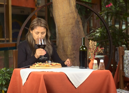 Beautiful young Peruvian woman smelling her red wine with eyes closed and eating pizza in a restaurant  photo
