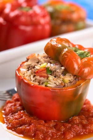 Baked stuffed red bell pepper filled with minced meat, onion, rice, tomato and green onion served on tomato sauce with casserole in the back (Selective Focus, Focus on the tomato piece and the stuffing around it on the top) Stock Photo - 9597864