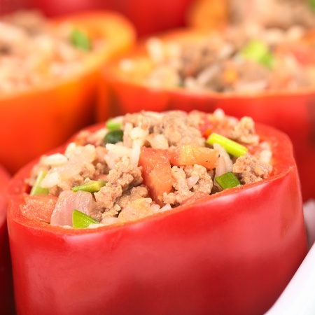 Stuffed red bell pepper filled with minced meat, onion, rice, tomato and green onion in a casserole (Selective Focus, Focus on the tomato piece in the front and the stuffing around it) photo