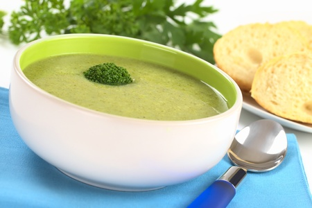 floret: Cream of broccoli garnished with a broccoli floret on top with baguette slices and parsley leaves in the back (Selective Focus, Focus on the broccoli floret on the soup) Stock Photo