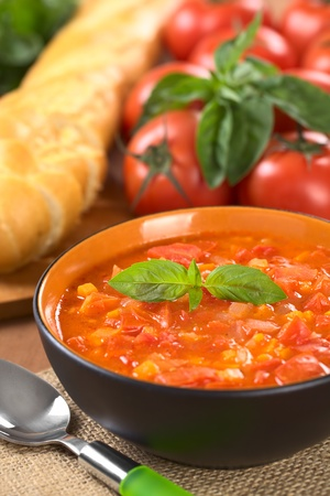 vegetable soup: Chunky tomato soup made of tomatoes, carrots and onions and garnished with a basil leaf (Selective Focus, Focus on the basil leaf on the soup) Stock Photo