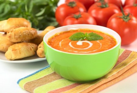 Cream of tomato with a spiral of cream on top and bread, tomatoes and basil leaves in the back (Selective Focus, Focus on the basil leaf in the bowl)