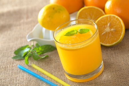 Freshly squeezed orange juice with orange slice and mint leaf on top of the juice (Selective Focus, Focus on the mint leaf on top of the juice) photo