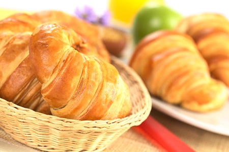 Fresh croissants in bread basket with a red knife beside, and a plate with croissants, green apple and orange juice in the back (Selective Focus, Focus on the front of the croissant in the basket) photo