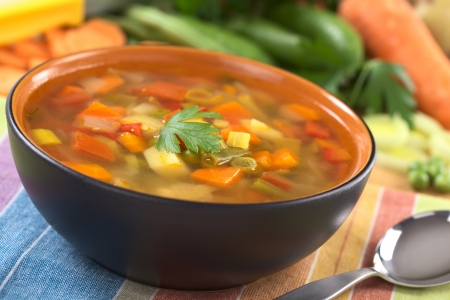 Fresh vegetable soup made of green bean, pea, carrot, potato, red bell pepper, tomato and leek in black bowl garnished with a parsley leaf with ingredients in the back (Selective Focus, Focus on the front of the parsley leaf) Stock Photo - 9644798