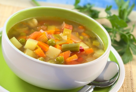 Fresh vegetable soup made of green bean, pea, carrot, potato, red bell pepper, tomato and leek in bowl with parsley in the back (Selective Focus, Focus on the vegetables one third into the soup) Stock Photo