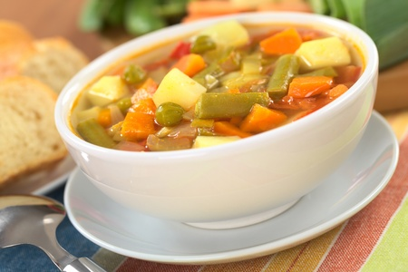 Fresh vegetable soup made of green bean, pea, carrot, potato, red bell pepper, tomato and leek in white bowl with baguette slices and ingredients in the back (Selective Focus, Focus on the vegetables one third into the soup) photo
