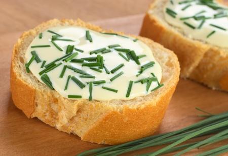 Baguettescheiben mit Frischkäse und Schnittlauch auf Schneidebrett (Selective Focus, Focus auf der Vorderseite des ersten Baguette) Standard-Bild