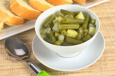 Green bean and potato hotpot in white bowl with a spoon beside and baguette slices in the back (Selective Focus, Focus on the first half of the hotpot) Stock Photo - 9691356