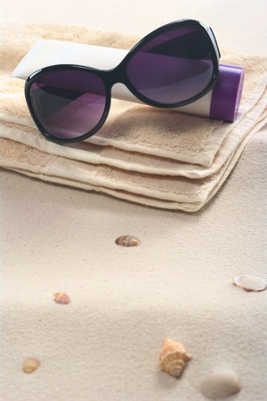 Beach setting with sunglasses, suncream and towels on sand with shells (Selective Focus, Focus on the sunglasses) photo