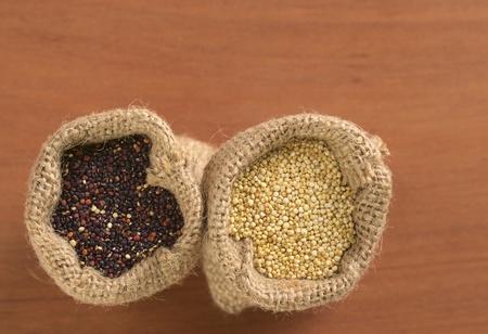 木材にジュート袋に生の赤と白のキノア粒。キノアはアンデス地方で栽培されており、高たんぱく含量と栄養価の高い (セレクティブ フォーカス、