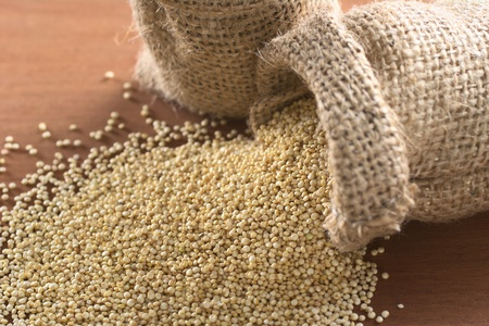 valued: Raw white quinoa grains in jute sack on wood. Quinoa is grown in the Andes and is valued for its high protein content and nutritional value (Selective Focus, Focus one third into the quinoa)