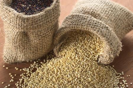 sacco juta: Raw quinoa grani bianchi in sacco di juta su legno con quinoa rossa in regola altro sacco. Quinoa viene coltivato nelle Ande ed � apprezzata per il suo alto contenuto proteico e il valore nutrizionale (attenzione selettiva, Focus sulla quinoa bianca all'apertura del sacco)