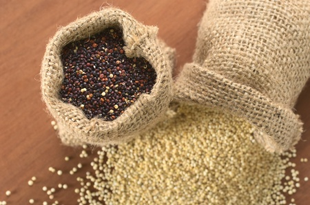 valued: Raw red quinoa grains in jute sack on wood, with white quinoa lying beneath. Quinoa is grown in the Andes and is valued for its high protein content and nutritional value (Selective Focus, Focus on the red quinoa)