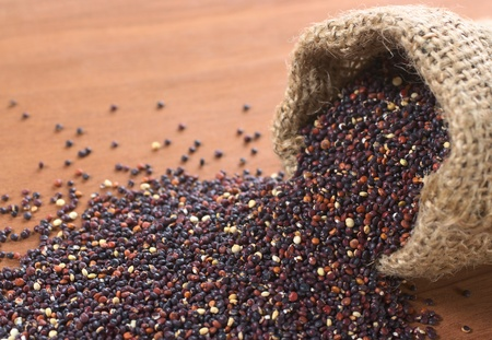 red quinoa: Raw red quinoa grains in jute sack on wood. Quinoa is grown in the Andes and is valued for its high protein content and nutritional value (Selective Focus, Focus on the quinoa in the first part of the sack running through the picture to the left)