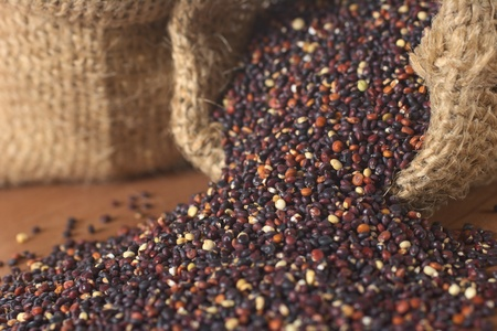 Raw red quinoa grains in jute sack on wood. Quinoa is grown in the Andes and is valued for its high protein content and nutritional value (Selective Focus, Focus on the quinoa at the right sack opening running through the picture to the left corner) photo
