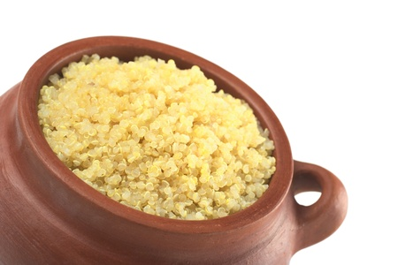 Cooked white quinoa in rustic bowl which can be eaten as a side dish like rice and is rich in proteins isolated on white (Selective Focus, Focus on the front of the quinoa)  photo