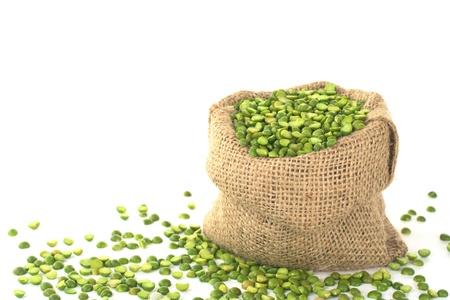 分割乾燥グリーン ピース白 (セレクティブ フォーカス、前袋の中の豆に焦点を当てる) にジュートの袋に