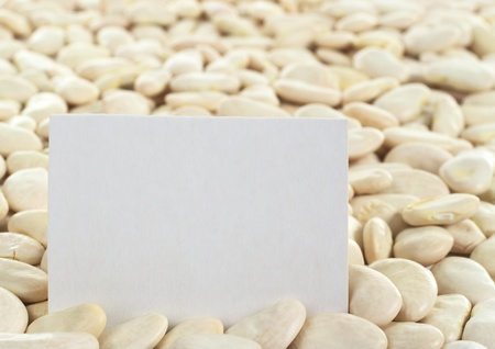 haba: Dried raw butter bean or also called lima bean (lat. Phaseolus lunatus) with a blank card (Selective Focus, Focus on the card) Stock Photo