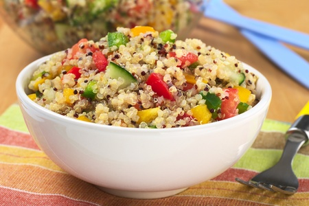 Delicious vegetarian quinoa salad with bell pepper, cucumber and tomatoes (Selective Focus, Focus one third into the bowl)  photo