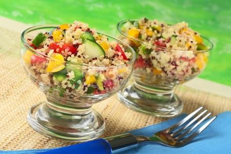 quinua: Ensalada de quinoa vegetariano delicioso en vidrio bowls con pimiento, pepino y tomates (enfoque selectivo, centrarse en la ensalada en el frente de la izquierda bowl)  Foto de archivo