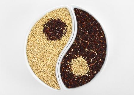 quinua: S�mbolo de Yin y Yang hecha de granos de quinua rojo y blanco crudo mediante dos cuencos en blanco