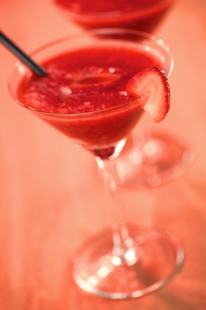 Frozen Strawberry Daiquiri Made of rum, strawberries, ice, sugar and lemon juice served in a cocktail glass with a strawberry slice on the rim and a black straw photographed with a red lighting filter on wood (Very Shallow Depth of Field, Focus on the fro photo