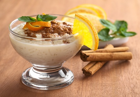 Delicious homemade rice pudding with cinnamon garnished with orange peel and mint leaf and a slice of orange on the rim of the bowl  photo