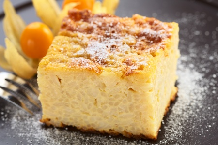 Baked rice pudding dessert sweetened with sugar powder and garnished with physalis in the back with a fork on the side  photo