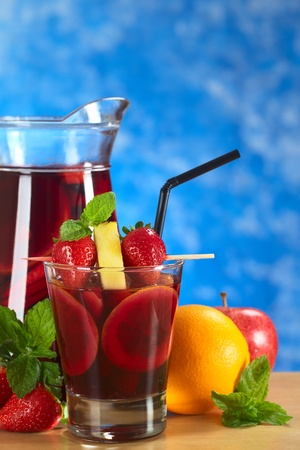 Refreshing red wine punch called sangria mixed with orange, apple and mango, garnished with strawberries and pineapple on skewer with a jug of sangria in the back and fruits around