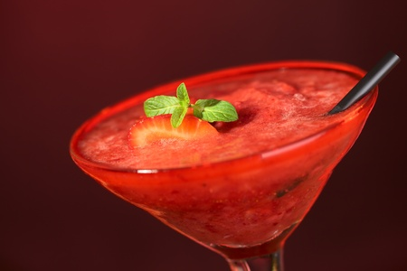 Frozen Strawberry Daiquiri made of rum, strawberries, ice, sugar and lemon juice served in a cocktail glass with a strawberry slice and a mint leaf in the drink and a black straw on the side Stock Photo - 9972928