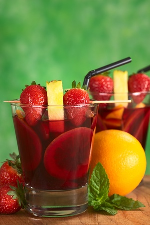 Two glasses of refreshing red wine punch called sangria mixed with orange, apple and mango, garnished with strawberries and pineapple on skewer surrounded by fruits photo