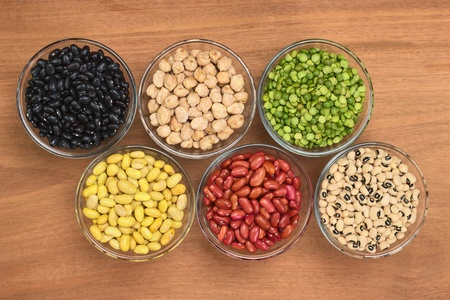 A variety of legumes (black beans, chickpeas, slit peas, canary beans, kidney beans and black-eyed peas) in glass bowl photographed on wood from above  photo