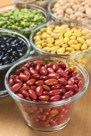 Kidney beans and other legumes (black beans, canary beans, split peas, chickpeas) in glass bowls photo