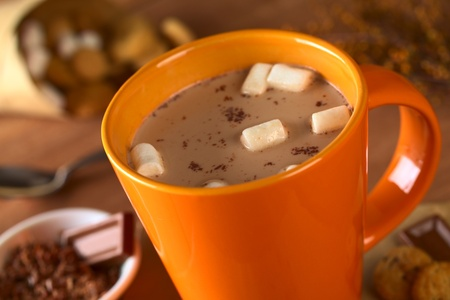 marshmallow: Hot chocolate with marshmallows in orange cup surrounded by chocolate and cookies (Selective Focus, Focus on the marshmallows in the middle of the hot chocolate)