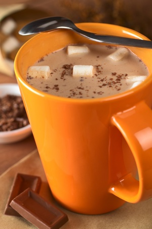 marshmallow: Hot chocolate with marshmallows in orange cup with a teaspoon on the rim and chocolate pieces on the side (Selective Focus, Focus on the marshmallows in the middle of the hot chocolate)