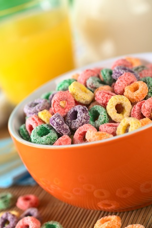 Colorful cereal loops with different fruit flavour in orange bowl with orange juice and milk in the back (Selective Focus, Focus one third into the bowl) photo