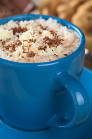 Hot chocolate with whipped cream and chocolate shavings in blue cup with cookies and chocolate in the back (Selective Focus, Focus on the top of the cream) photo