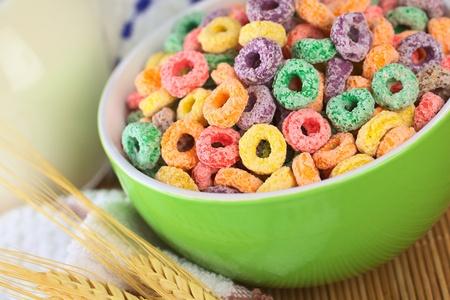 cereal: Crea un bucle de cereales colorido con sabor de frutas diferentes en Bol verde con leche en la espalda (enfoque selectivo, enfoque un tercio en el bowl)