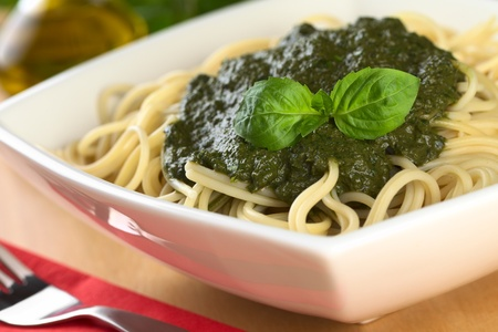 Fresh homemade pesto made of basil, garlic and olive oil served on spaghetti and garnished with a basil leaf (Selective Focus, Focus on the basil leaf on the pesto) photo