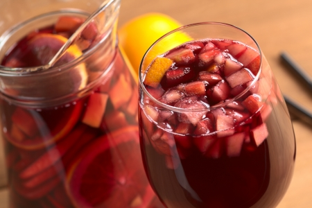 Refreshing red wine punch called sangria mixed with orange, apple, mango pieces served in wine glass (Selective Focus, Focus on the fruit pieces in the middle of the glass) photo
