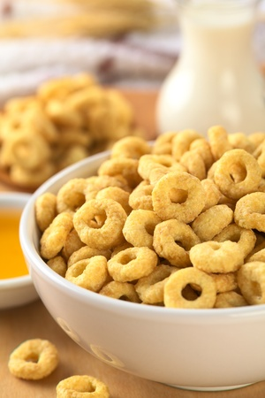 A bowl full of honey flavored cereal loops (Selective Focus, Focus on the standing cereal loop in the middle of the bowl) photo